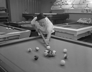 Sid playing pool with a shotgun.
