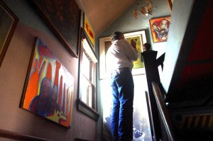 Jim Hirsch of Paul Davis Restoration investigates the stairwell of Sid's house. Steve Boyum's paintings are seen on the walls. (August, 2015)